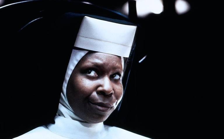 Mulher negra vestida de freira reflete