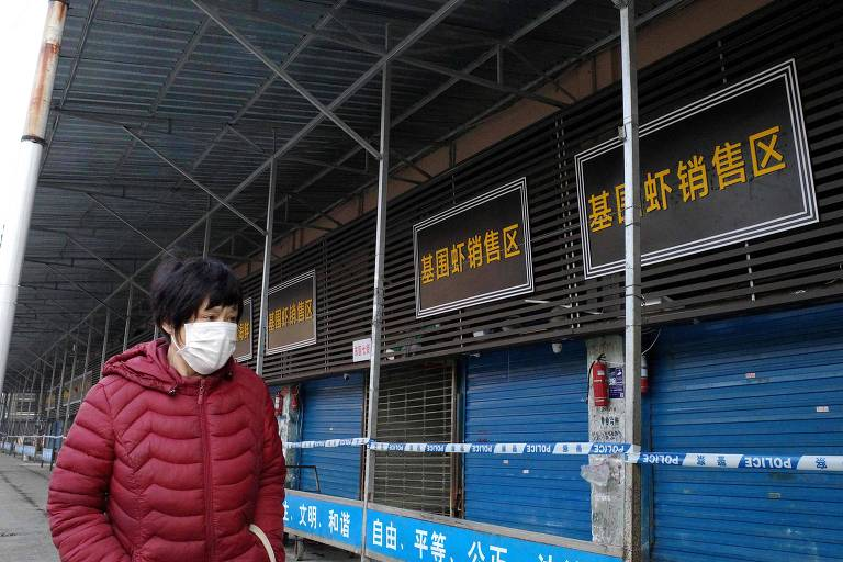 Mulher com máscara passa em frente a mercado de frutos do mar em Wuhan, onde surgiram os casos de infecção pelo novo coronavírus