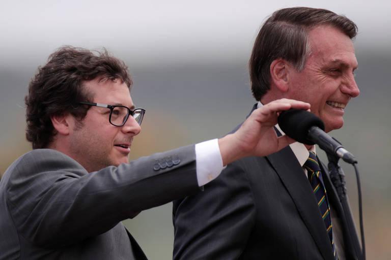 à esquerda, Fabio Wajngarten ajusta microfone para o presidente Jair Bolsonaro. Ambos são fotografados de perfil, olhando para a direita e sorrindo