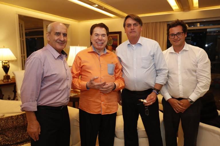 Da esquerda para a direita, o general Luiz Ramos, o apresentador Silvio Santos, o presidente Jair Bolsonaro e o chefe da Secretaria de Comunicação Social da Presidência da República, Fabio Wajngarten. Estão na sala de uma casa, posam sorrindo para a foto