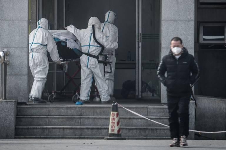 Membros da equipe médica transportam um paciente para o hospital Jinyintan, onde infectados por um vírus desconhecido estão sendo tratados, em Wuhan, na província central de Hubei, na China