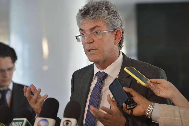 De terno cinza e gravata azulada, Ricardo Vieira Coutinho concede entrevista à imprensa. ele gesticula diante de microfones com logos de várias emissoras e há mãos e jornalistas segurando gravadores diante do governador.