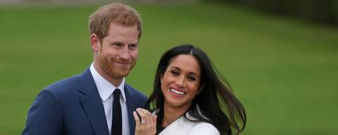 (FILES) In this file photo taken on on November 27, 2017, Britain's Prince Harry stands with his fiancee US actress Meghan Markle as she shows off her engagement ring whilst they pose for a photograph in the Sunken Garden at Kensington Palace in west London, following the announcement of their engagement. - Britain's Prince Harry and his wife Meghan will give up their titles and stop receiving public funds following their decision to give up front-line royal duties, Buckingham Palace said on January 18, 2020.