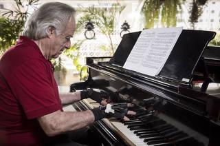 ***Especial para Domingo.FOLHA*** Maestro e Pianista Joao Carlos Martins testa luva eletronica em seu piano na sala de seu apartamento no Jardins.  Com a  luva Maestro  chega a usar 9 dos 10 dedos. Anteriormente ele conseguia tocar  piano apenas  com dois dedos
