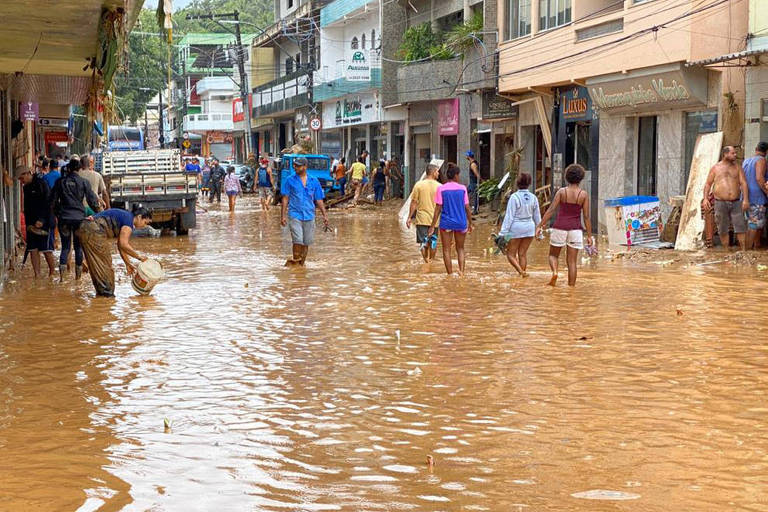 Pessoas caminham em rua alagada de Iconha, no Espírito Santo