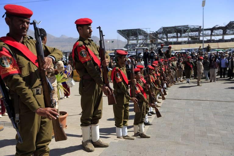 Militares em desfile fazem fila um ao lado do outro. Os uniformes são verdes e têm boinas e faixas vermelhas. Portam fuzis