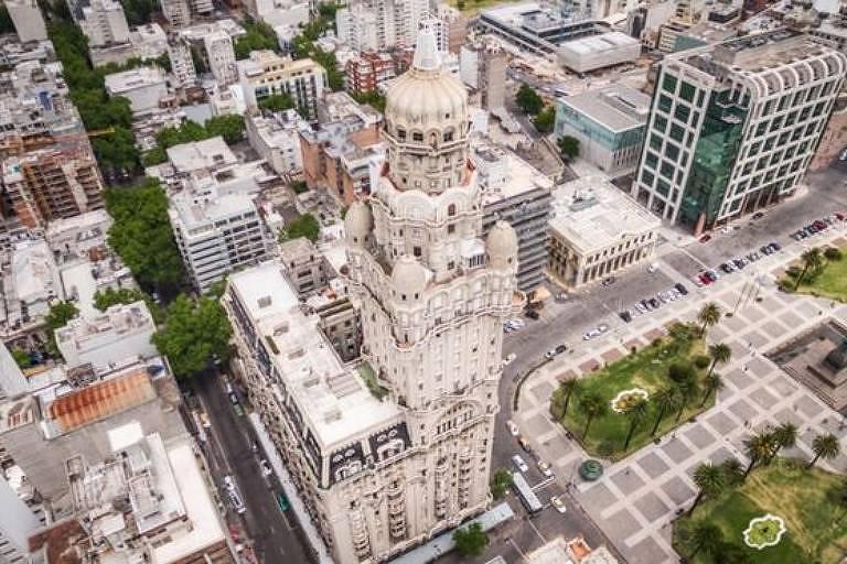 foto mostra vários prédios vistos de cima em grande centro urbano. à direita, praça com árvores
