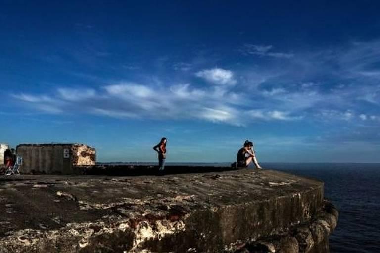 foto mostra grande pedra onde há uma mulher sentada. Atrás dela está uma outra mulher em pé. Há pessoas sentadas em cadeiras de praia, desfocadas. Ao fundo está o mar. O céu é azul e com poucas nuvens brancas