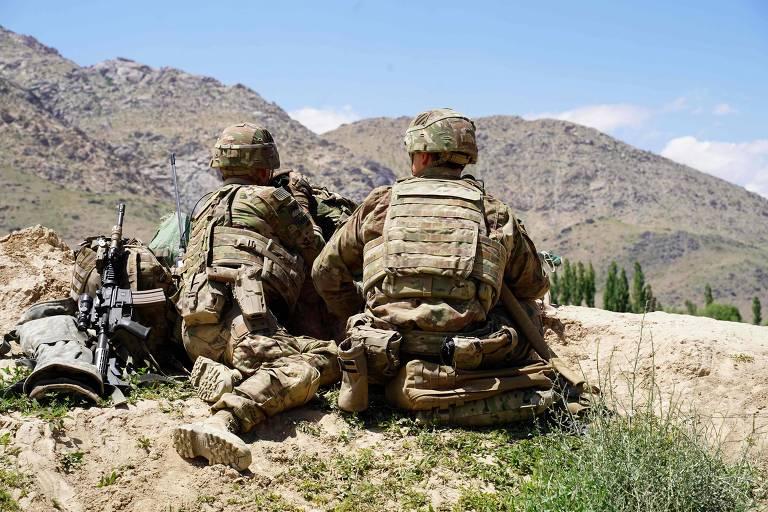 Dois soldados fardados sentados no chão, com um mato ralo. Ao fundo, uma paisagem de montanhas.