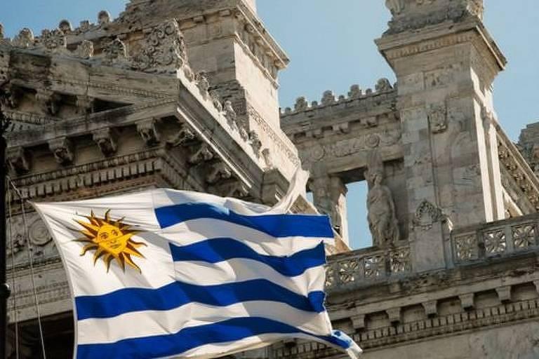 foto mostra bandeira do uruguai, que tem um sol com rosto em um quadrado de fundo branco do lado esquerod superior. O resto da bandeira é de faixas brancas e azuis na horizontal. Ao fundo, um  prédio de mármore