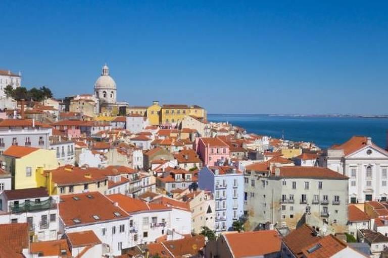 foto mostra diversas casas. A maioria tem paredes em cores claras, algumas azuis, outras amarelas e rosas. Todas possuem telhados laranjas. Ao fundo, do lado direito, está o mar.