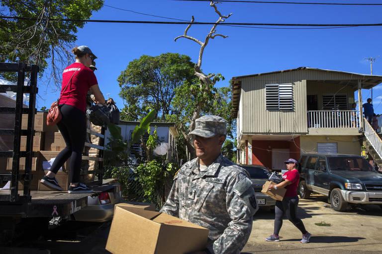 Militares e voluntários distribuem água e alimentos para os moradores de Isabela atingidos pelo furacão Maria