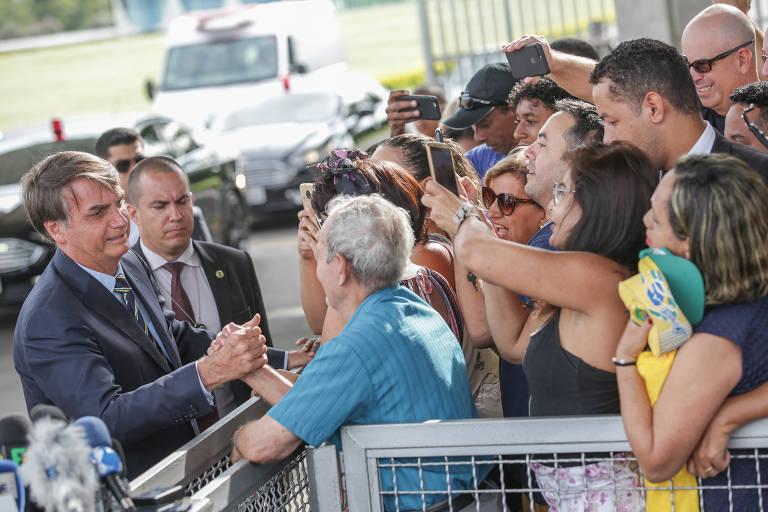 à esquerda, o presidente aparece e se dirige ao grupo de apoiadores e jornalistas, separados por um portão. Algumas pessoas levantam seus celulares para registrar o momento