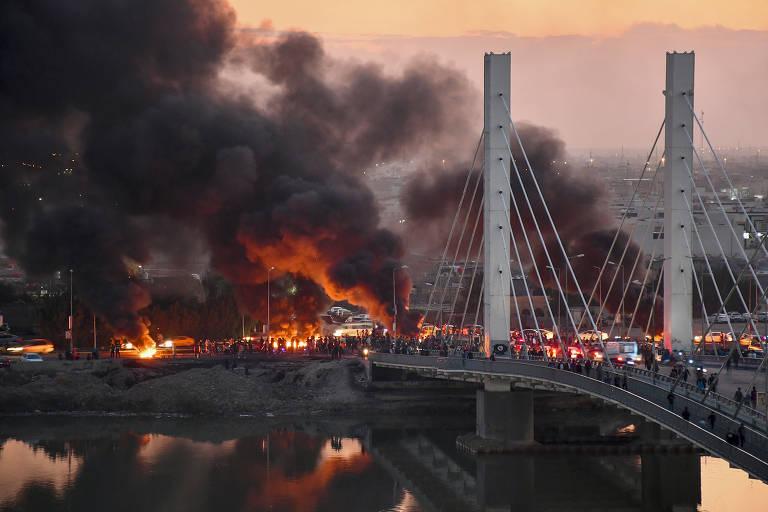 Ponte envolta de fumaça escura e densa, ainda pegando fogo