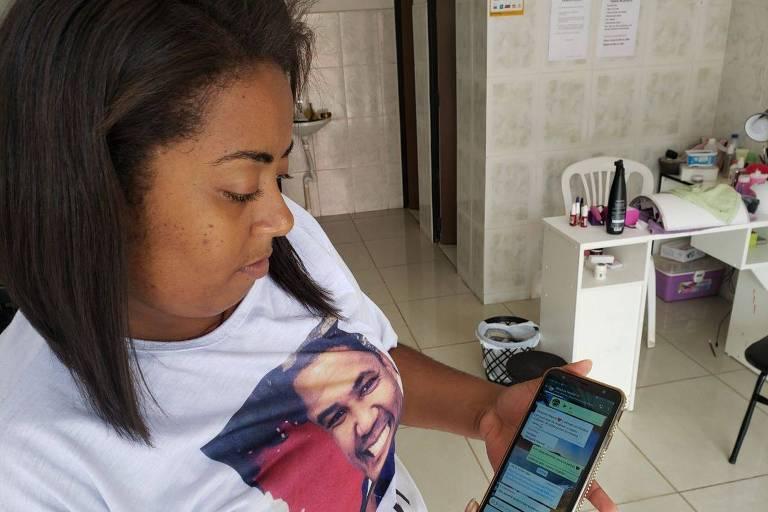 """Nayara Cristina Dias Porto Ferreira, 28, que perdeu o marido no rompimento da barragem da Vale, em Brumadinho (MG). Ela tem um salão de beleza e mostra o grupo de WhatsApp """"Nossos Heróis"""", que reúne viúvas"""