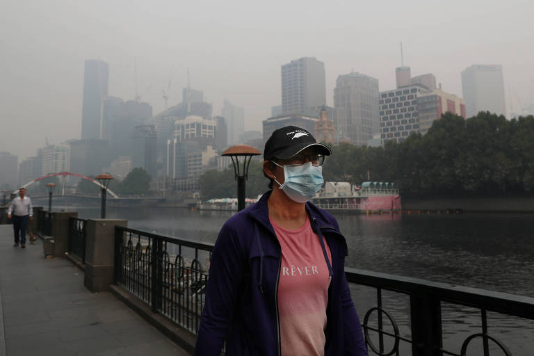 Morador de Melbourne, na Austrália, usa máscara para se proteger das fumaças