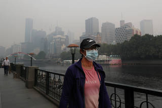 People wear breathing masks to protect themselves from a thick smoke haze from the bushfires, in Melbourne