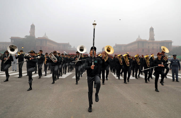 Dezenas de homens uniformizados carregando instrumentos musicais caminham enfileirados e em passo sincronizado em uma rua