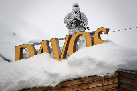(FILES) In this file photo taken on January 21, 2019, policeman wearing camouflage clothing stands on the rooftop of a hotel, next to letters covered in snow reading 'Davos', near the Congress Centre ahead of the World Economic Forum (WEF) annual meeting in Davos, eastern Switzerland. - The World Economic Forum 50th Annual Meeting in Davos is held from January 21 to 24, 2020. (Photo by Fabrice COFFRINI / AFP)