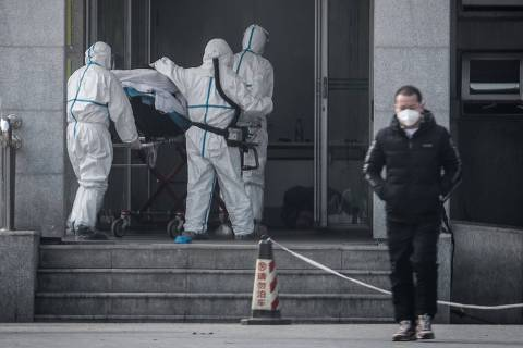 (FILES) This file photo taken on January 18, 2020 shows medical staff members carrying a patient into the Jinyintan hospital, where patients infected by a mysterious SARS-like virus are being treated, in Wuhan in China's central Hubei province. - A mysterious SARS-like virus has spread around China -- including to Beijing -- authorities said on January 20, 2020, fuelling fears of a major outbreak as millions begin travelling for the Lunar New Year in humanity's biggest migration. (Photo by STR / AFP) / China OUT