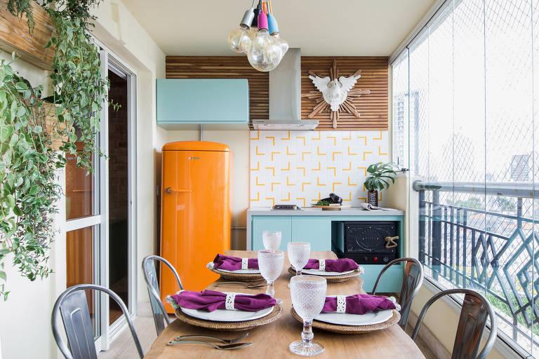 Arquiteta Julia Varon transformou a varanda espaçosa, mas pouco utilizada, do apartamento dos anos 1990 em cozinha completa, com forno de pizza, geladeira cor de abóbora e mesa para quatro lugares