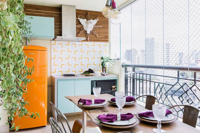 Varanda com mesa posta, com taças e guardanapo de pano roxo em cima dos pratos. Ao fundo, uma geladeira laranja e uma planta em um vaso pendente