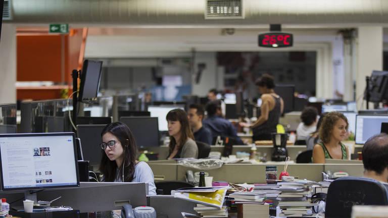 Jornalistas trabalham em suas mesas na Redação