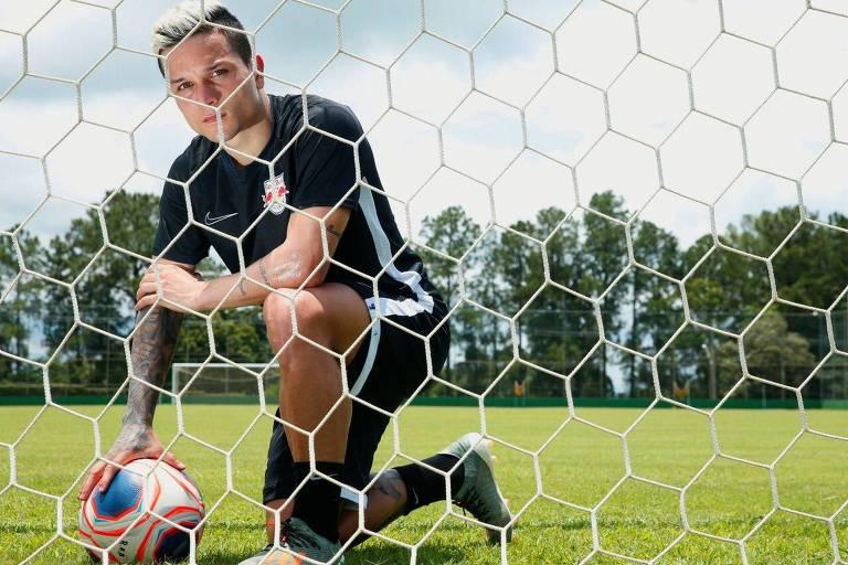 Jogador ajoelhdo segura a bola com a mão direita