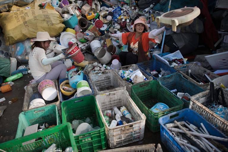 Trabalhadores chineses separam garrafas de plástico em centro de descarte em Pequim