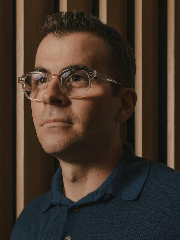 Retrato de Adam Mosseri; a foto está focada no rosto. O executivo tem óculos com armação transparente e usa uma camisa polo azul marinho. seu cabelo é curto e tem corte moderno