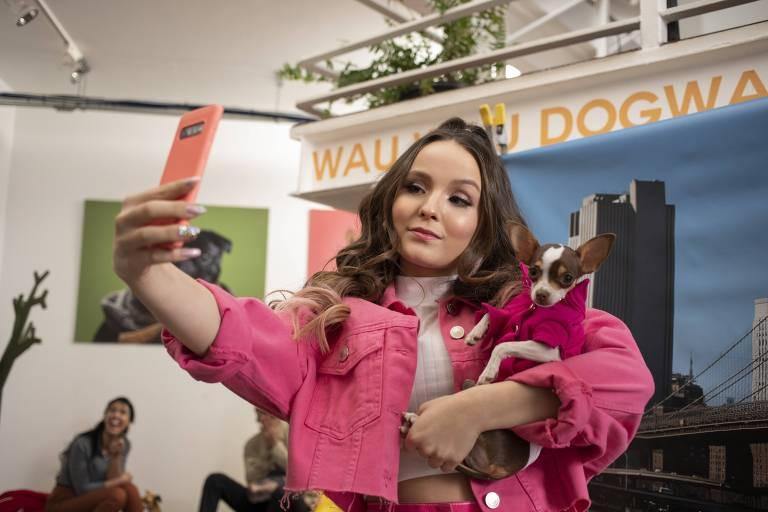 menina vestida de rosa tira selfie com cachorro nos braços