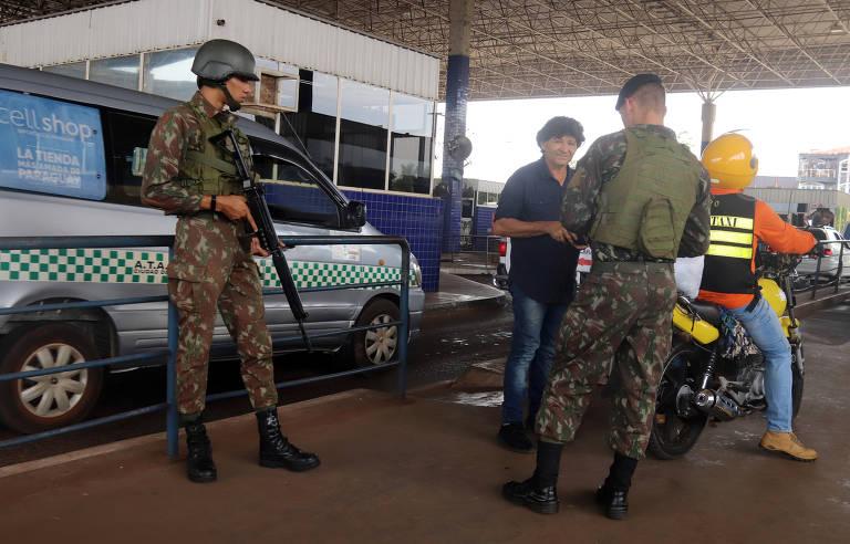 dois militares fardados, um deles segurando um fuzil, olham documento de homem ao lado de uma moto