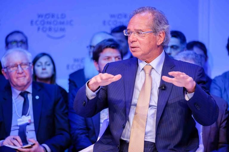 Retrato do ministro da Economia; Paulo Guedes usa um terno azul, gravata dourada e camisa azul claro. Ele faz um gesto com as mão estendidas