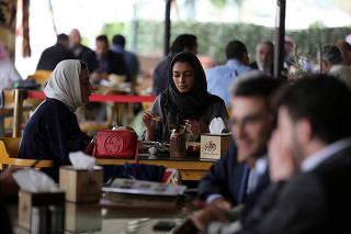 Saudi men and women sit at cafe in Riyadh