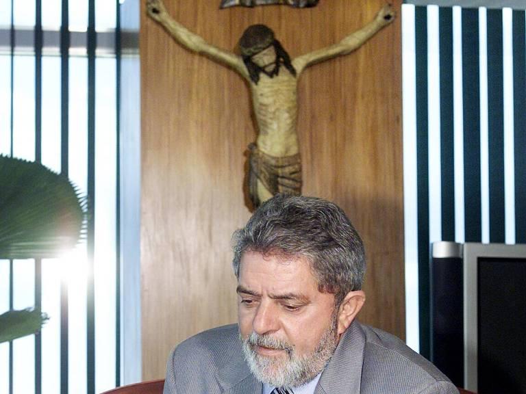 O então presidente Lula lê panfleto no Palácio do Planalto, em 2003, com crucifixo ao fundo