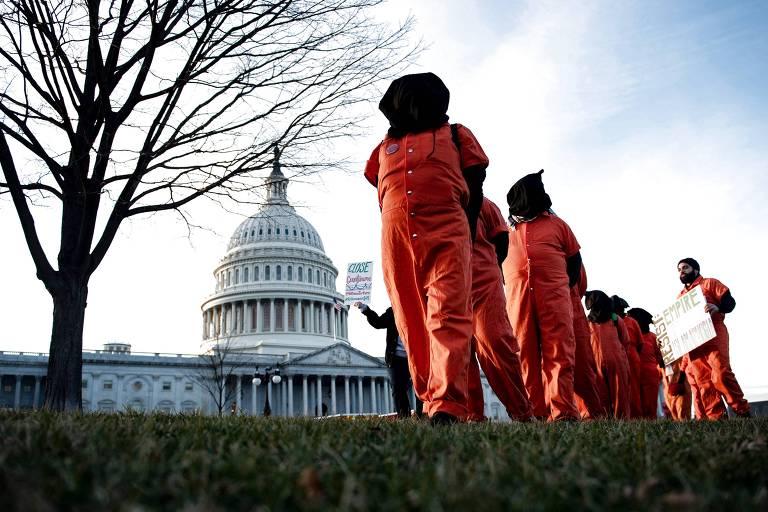 pessoas com macacões laranja e capuzes pretos andam em fila indiana, com o capitólio ao fundo