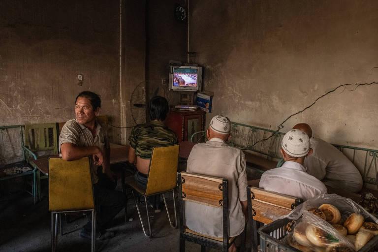 Homens uigures assistem a um filme em casa de chá de Yarkand