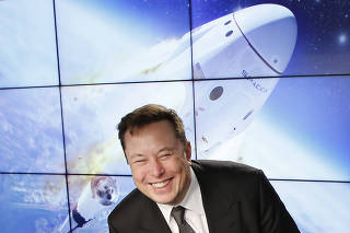 SpaceX founder and chief engineer Elon Musk reacts at a post-launch news conference to discuss the  SpaceX Crew Dragon astronaut capsule in-flight abort test at the Kennedy Space Center