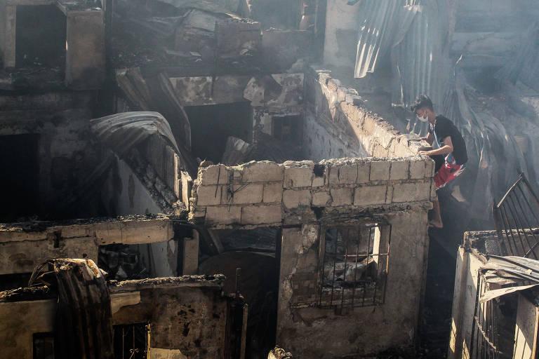 Homem sobe em parede e observa o interior de uma casa destruída pelo fogo