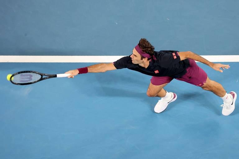 Federer estica o braço com a raquete na mão em direção à bola