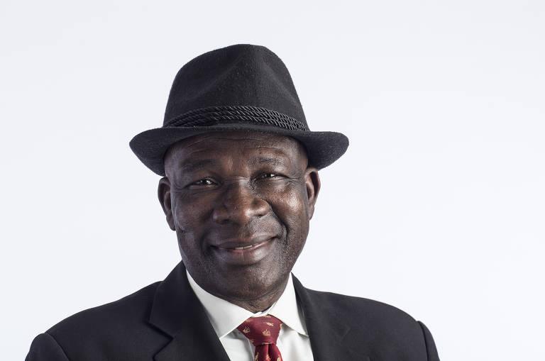 Senhor negro sorri. Ele veste um chapéu preto e um terno preto, com camisa branca e gravata vermelha