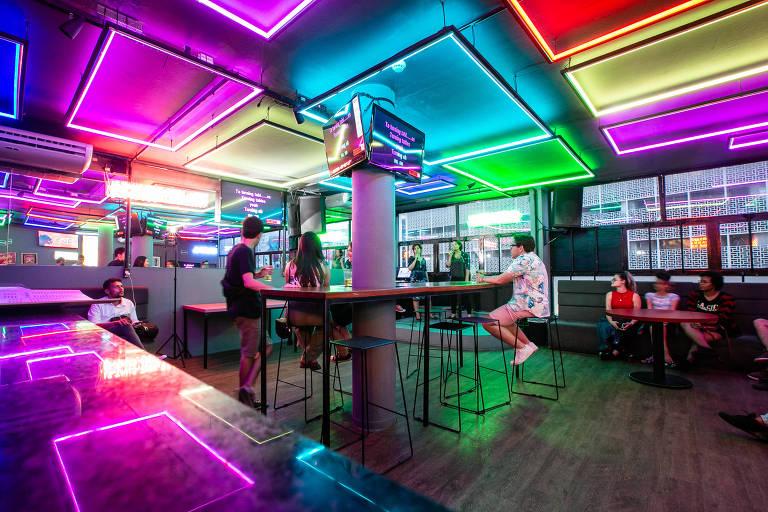 Pessoas cantam em espaço com luzes em néon de várias cores no teto. Janelas ao fundo mostra prédio do centro da cidade de São Paulo