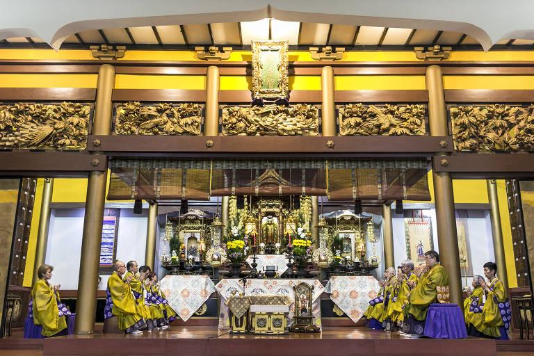 Monges com roupas amarelas sentados em altar decorado itens dourados