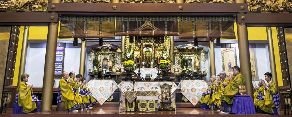 Monges de amarelo em altar de templo com muita madeira e dourado