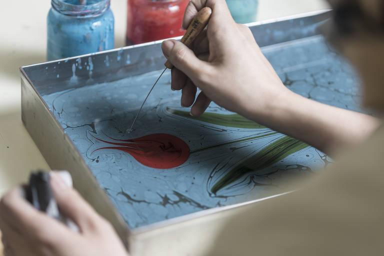 Professora Güzin Cobanoglu, que nasceu na Turquia, mostra técnica de pintura turca em seu ateliê em São Paulo