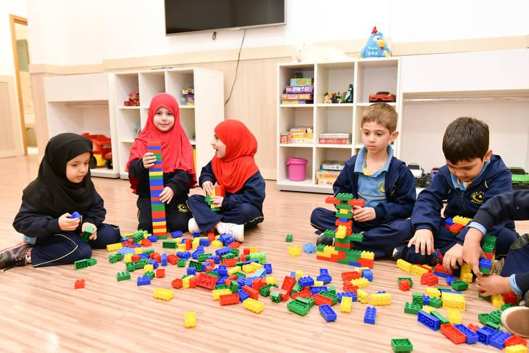 Três meninas com véu islâmico e dois meninos com uniforme. Os cinco brincam de lego sentados no chão