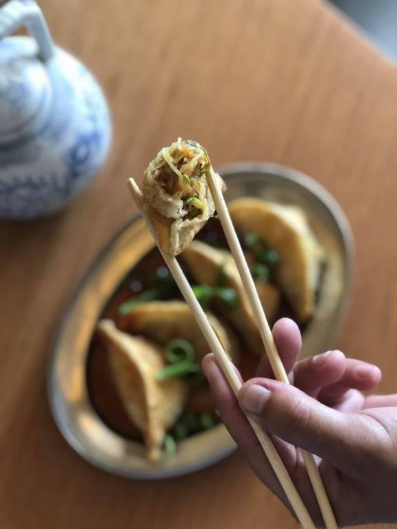 Pessoa segura um guioza recheado de macarrão do tipo bifum, receita especial do Panda Ya para celebrar o Ano-Novo chinês