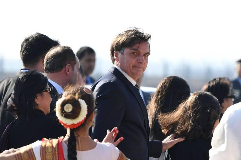 Retrato do presidente, que olha para a câmera, rodeado de de assessores; uma dançarina indiana faz um a coreografia ao lado de Jair Bolsonaro