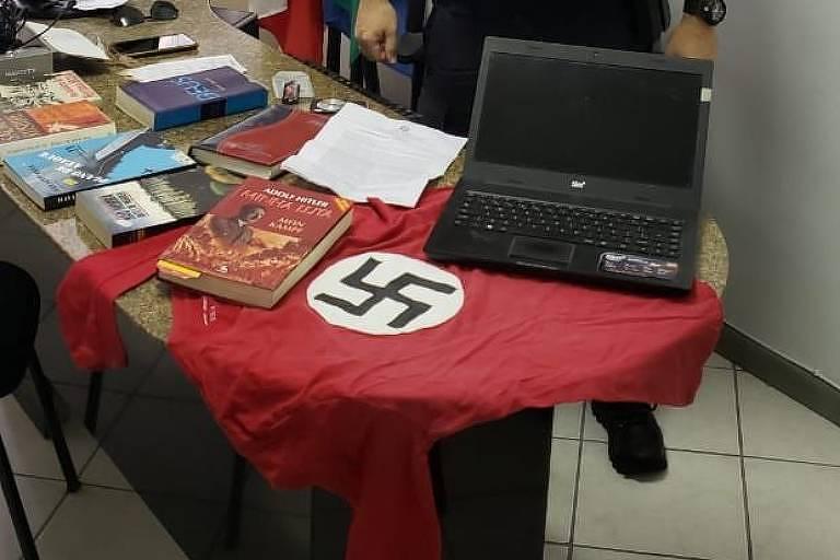Livros com apologia ao nazismo foram apreendidos na casa de homem que pendurou suástica na janela
