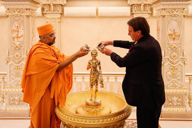 mestre religioso hindu e homem de terno despejam água